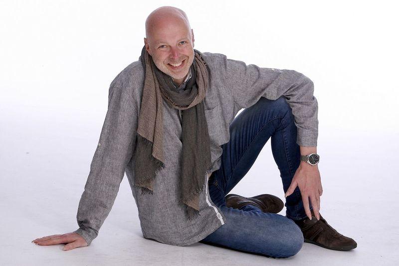 Mann mit grauem Pullover, Schal und Jeans sitzt lässig auf dem Boden und lächelt in die Kamera