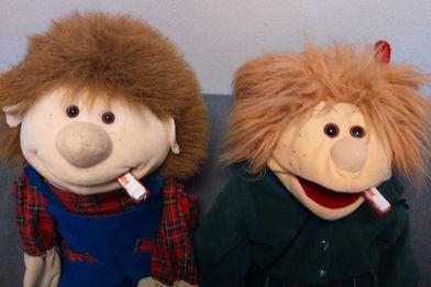 Die Handpuppen Lotti und Willi sitzen nebeneinander und haben einen Schokoriegel im Mund - Copyright: Ev.-Luth. Kirchengemeinde Schwarzenbek