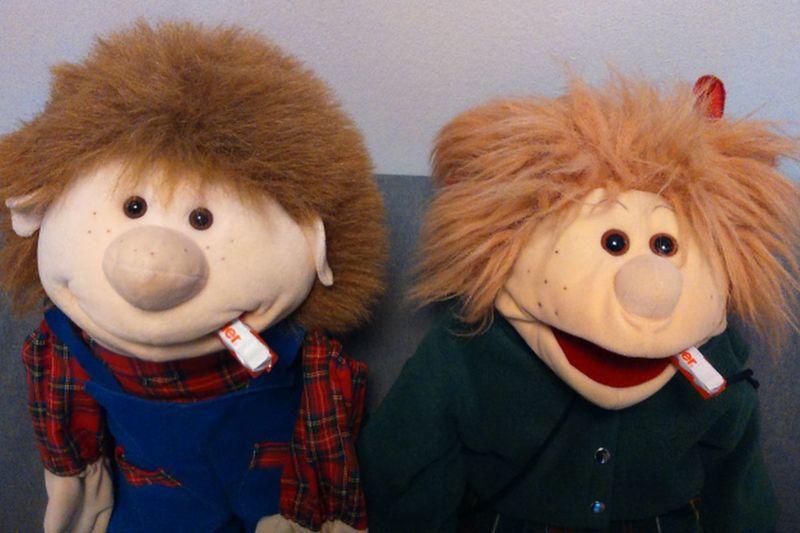 Die Handpuppen Lotti und Willi sitzen nebeneinander und haben einen Schokoriegel im Mund
