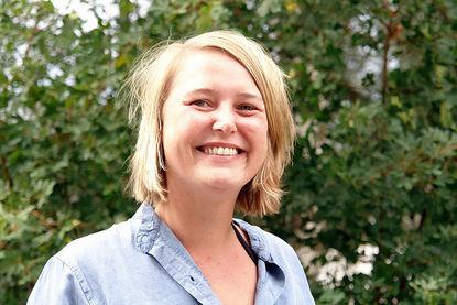 Portraitbild von Pastorin Sarah Stützinger, sie steht vor einer grünen Hecke. - Copyright: Ev.-Luth. Kirchengemeinde Schwarzenbek