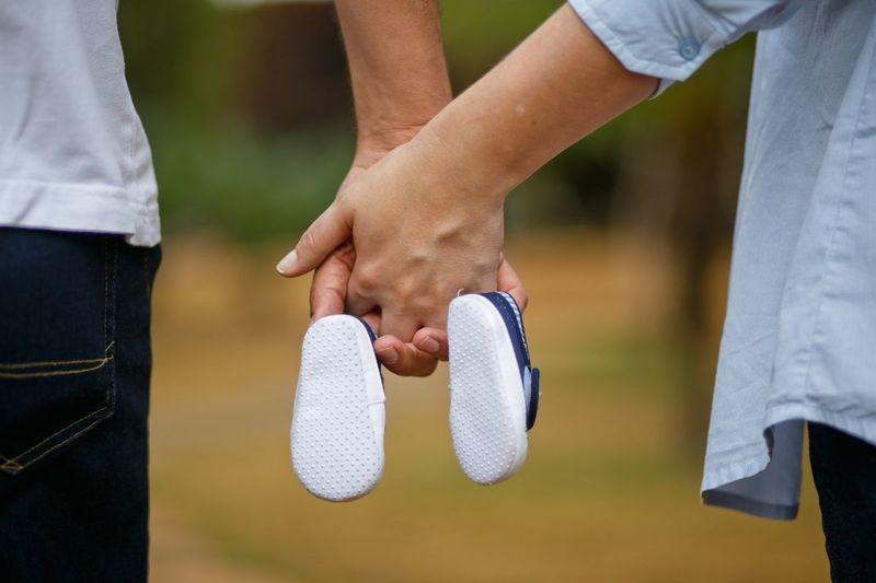 Hände von Mann und Frau die Babyschuhe in der Mitte halten