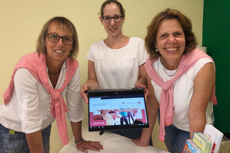 Conny Schermann (v. li.), Nadine Kukat und Kerstin Dlugi präsentierten das neue Programm der Familienbildungsstätte Schwarzenbek stehen am Tisch, haben ein Tablet in der Hand, auf dem die neue Homepage zu sehen ist..