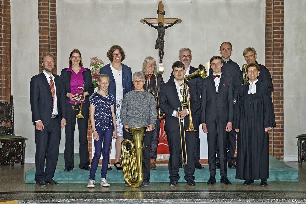 Erwachsene und Jugendliche mit Blechblasinstrumenten mit einer Pastorin in der Kirche - Copyright: Ev.-Luth. Kirchengemeinde Schwarzenbek