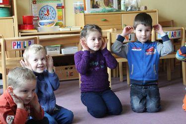 Dreii Jungs und ein Mädchen sitzen im Kindergarten auf dem Boen un halten die Hände an die Ohren zum Lauschen  - Copyright: Ev.-Luth. Kirchengemeinde Schwarzenbek