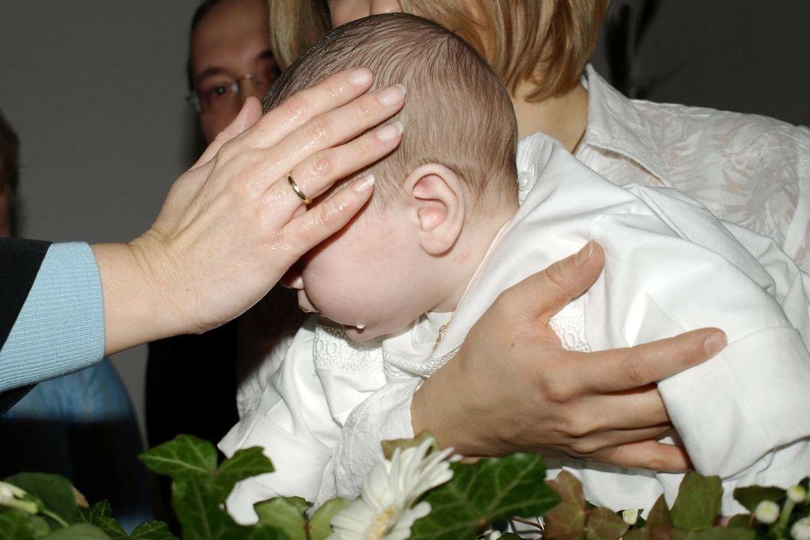 Kleines Kind wird über ein Taufbecken gehalten und es wird vom Pfarrer die Hand aufgelegt. - Copyright: pixabay baptism-331581_1920