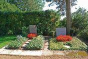 Zwei Gräber mit roten Blumen und Grabsteinen - Copyright: Ev.-Luth. Kirchengemeinde Schwarzenbek