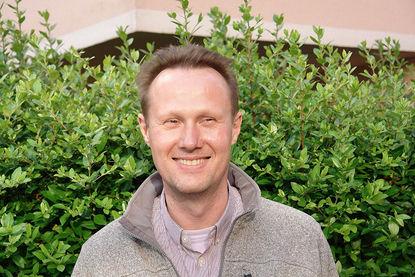 Portraitbild: Pastor Andreas Schöer steht vor einer grünen Hecke - Copyright: Ev.-Luth. Kirchengemeinde Schwarzenbek