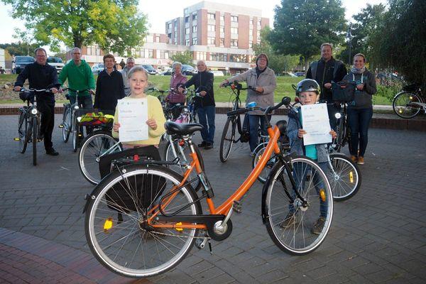 Ein Gruppe Menschen mit Fahrrädern, im Vordergrund ein oranges Fahrrad und zwei Kinder mit Urkunden - Copyright: Kirchengemeinde Schwarzenbek