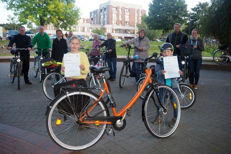 Ein Gruppe Menschen mit Fahrrädern, im Vordergrund ein oranges Fahrrad und zwei Kinder mit Urkunden