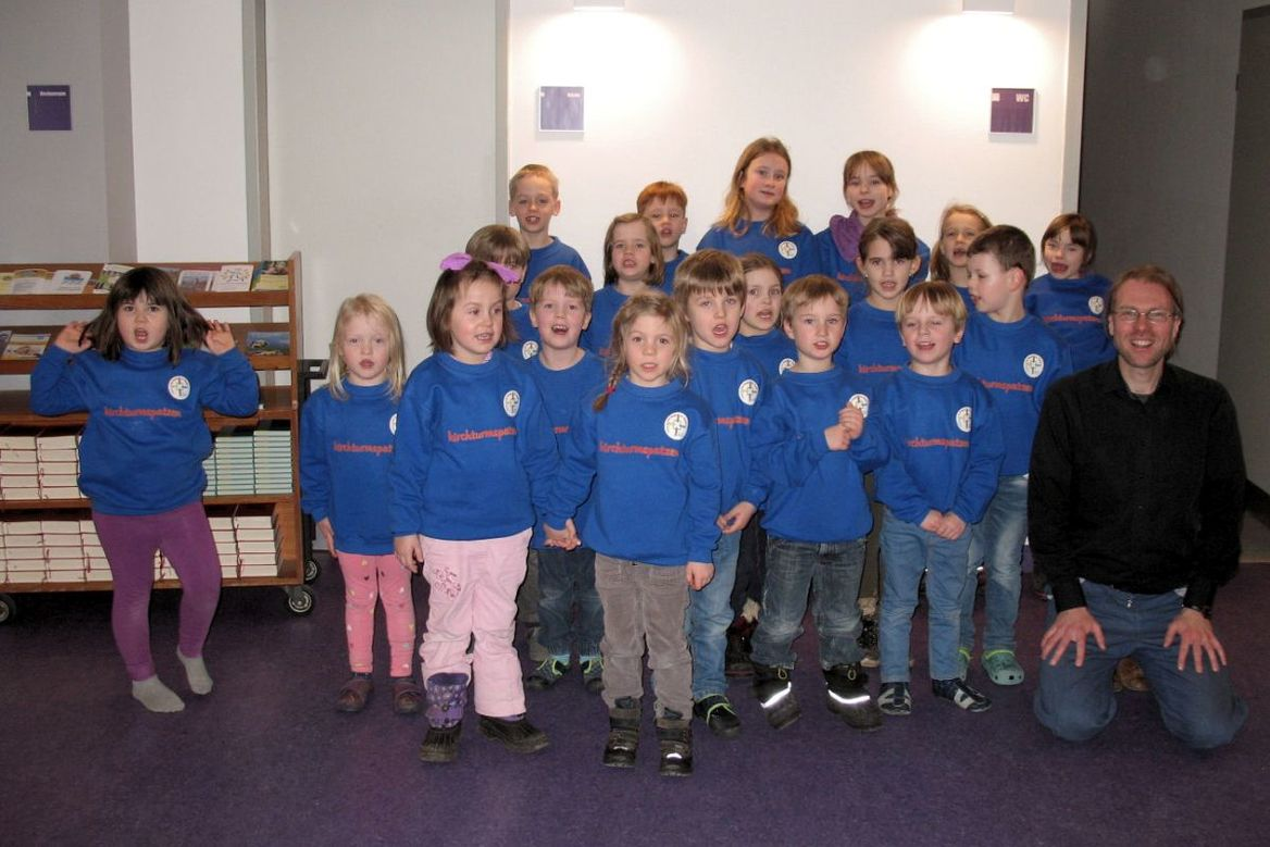 Kindergartenkinder alle in blauen Pullovern und ein knieender Chorleiter - Copyright: Ev.-Luth. Kirchengemeinde Schwarzenbek