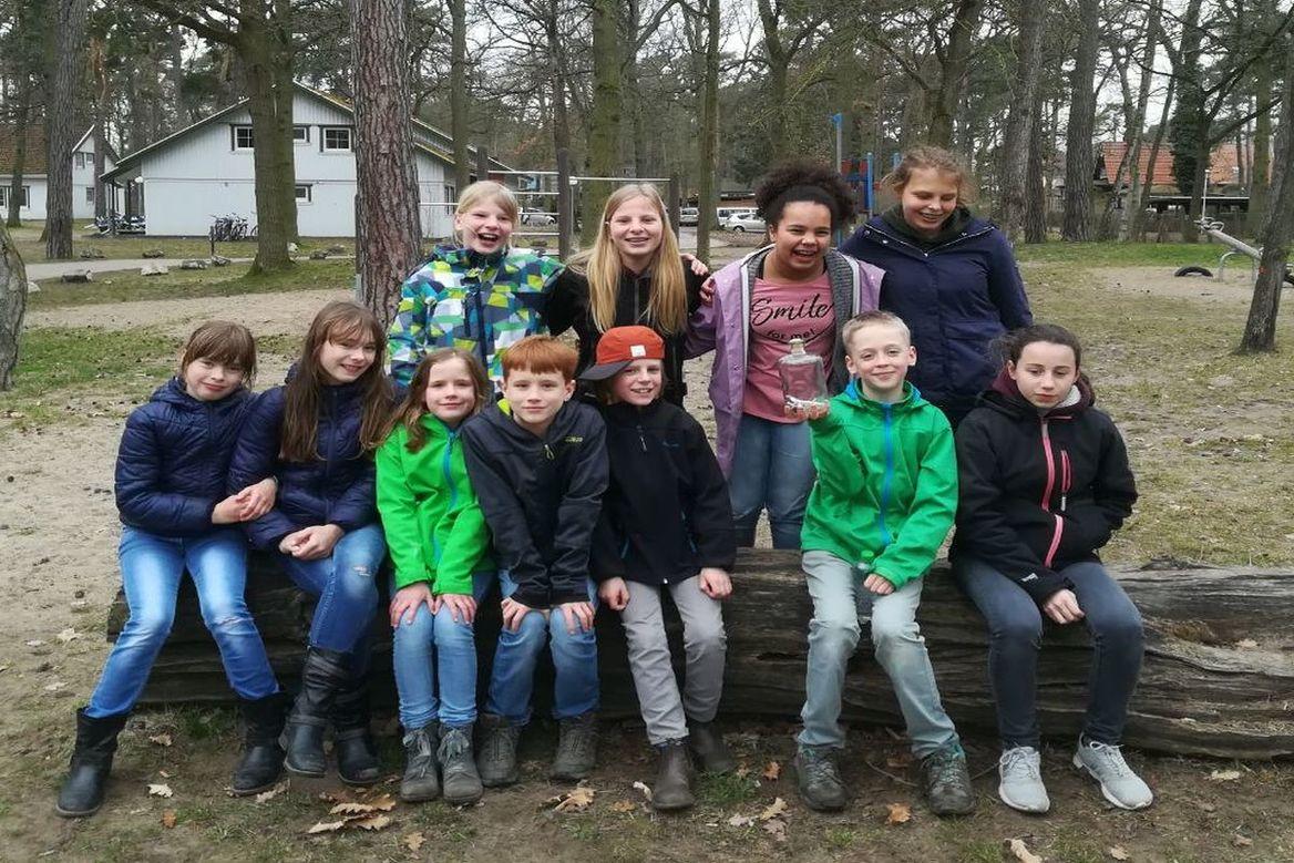 Kinder sitzen auf einem Baustamm, dahinter stehen noch weitere Kinder - Copyright: Ev.-Luth. Kirchengemeinde Schwarzenbek
