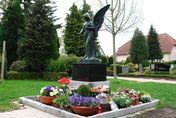 Engelfigur auf einem Sockel mit Blumen   - Copyright: Ev.-Luth. Kirchengemeinde Schwarzenbek