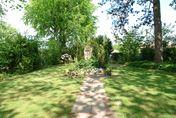 Grüner Park mit einem großen Grabstein - Copyright: Ev.-Luth. Kirchengemeinde Schwarzenbek