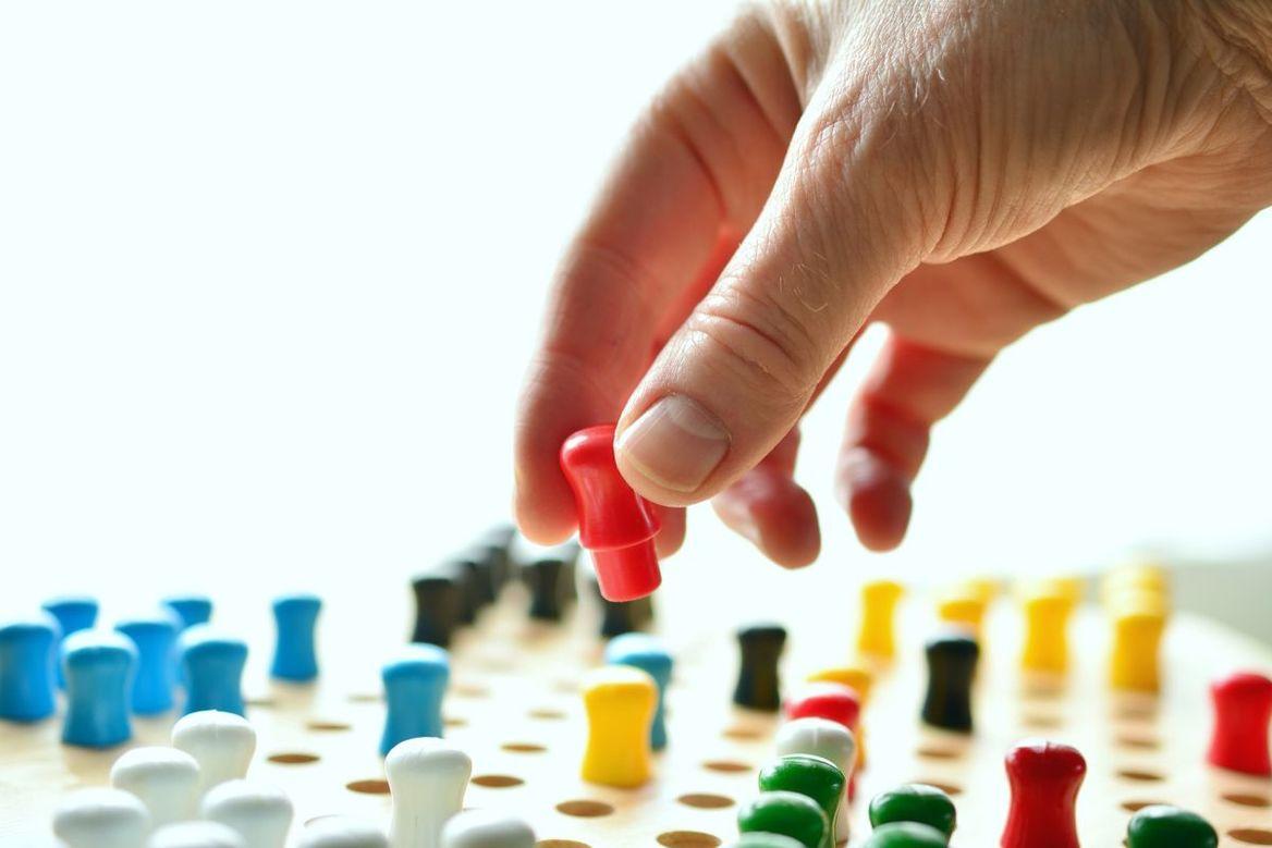 Spielbrett mit bunten Figuren, darüber eine Hand mit einer roten Spielfigur - Copyright: pixabay  2205340