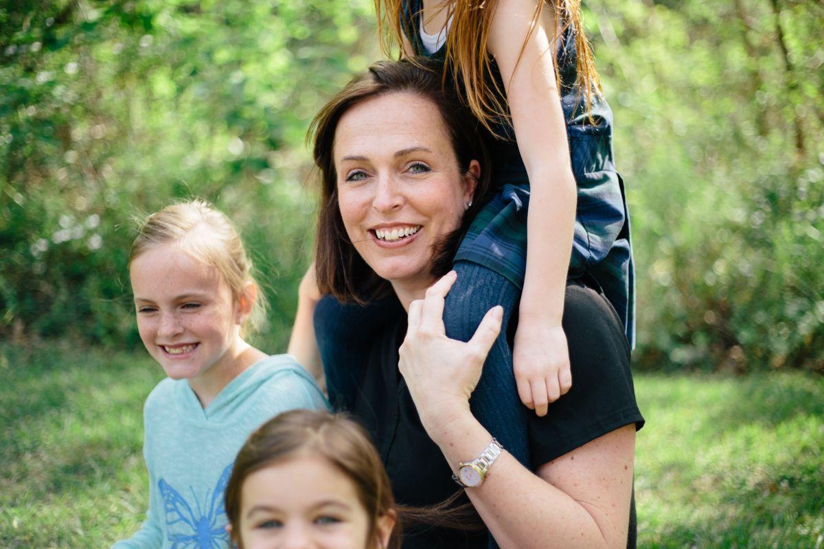 Mutter mit zwei Kindern neben sich und einem Kind auf den Schultern
