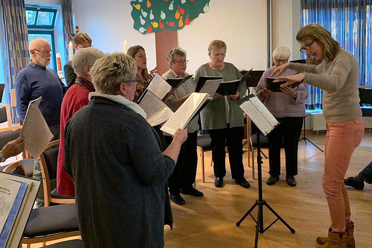 Rechts dirigiert die Chorleiterin Andrea van Bezouwen einige Mitglieder des Chors, die links stehen und singen.